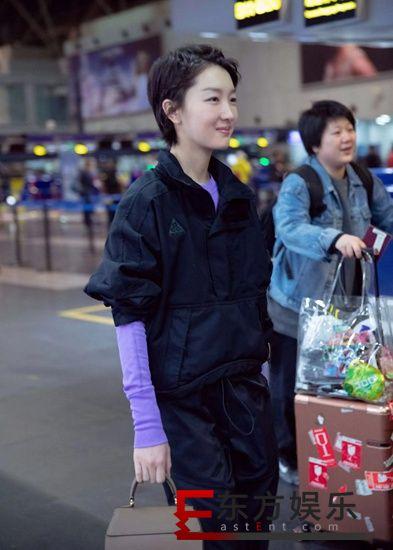 周冬雨黑色工装现身机场 紫色内搭明亮个性引人关注