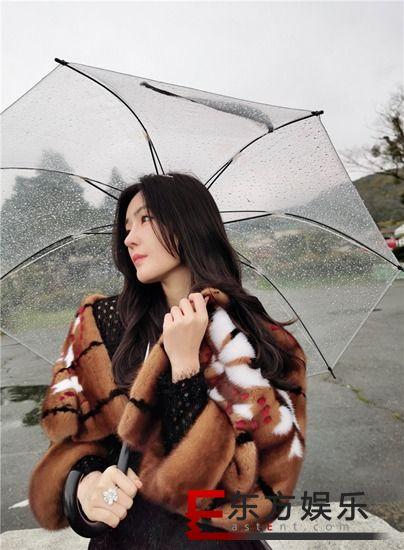 汤晶媚社交平台分享旅行美照  雨中漫步形似画中人